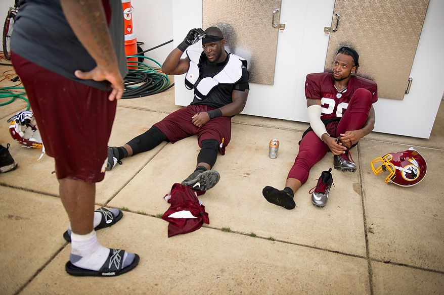 Washington Redskins linebacker Brian Orakpo (98), second from right,  defensive back Cedric Griffin (20), right, cool off in the shade following afternoon practice on the first day of training camp at Redskins Park, Ashburn, Va., Thursday, July 26, 2012. (Andrew Harnik/The Washington Times)