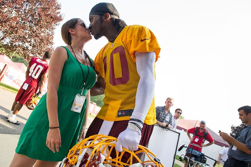 Washington Redskins quarterback Robert Griffin III (10) kisses his fiance Rebecca Liddicoat following afternoon practice on the first day of training camp at Redskins Park, Ashburn, Va., Thursday, July 26, 2012. (Andrew Harnik/The Washington Times)