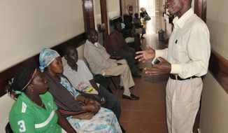 ** FILE ** In this Thursday, July 12, 2012, photo, a health worker from The AIDS Support Organization (TASO) health worker speaks with patients waiting for treatment in Kampala, Uganda. (AP Photo/Stephen Wandera)