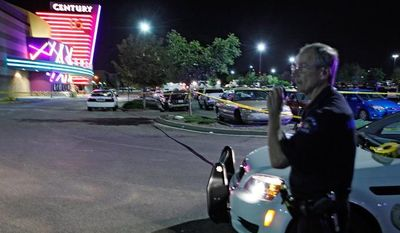 A police officer talks on his radio July 20, 2012, outside of the Century 16 theater at Aurora Mall in Aurora, Colo., where at least 14 people were killed and many injured at a shooting at the theater. (Associated Press)