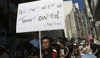 A protester holds a placard July 29, 2012, during a march in a downtown street in Hong Kong to protest the upcoming introduction in schools of Chinese patriotism classes that they fear will lead to brainwashing. (Associated Press)