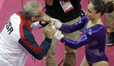 U.S. gymnast Jordyn Wieber, right, celebrates with head coach John Geddert during the Artistic Gymnastic women's qualifications at the 2012 Summer Olympics, Sunday, July 29, 2012, in London. (AP Photo/Julie Jacobson)