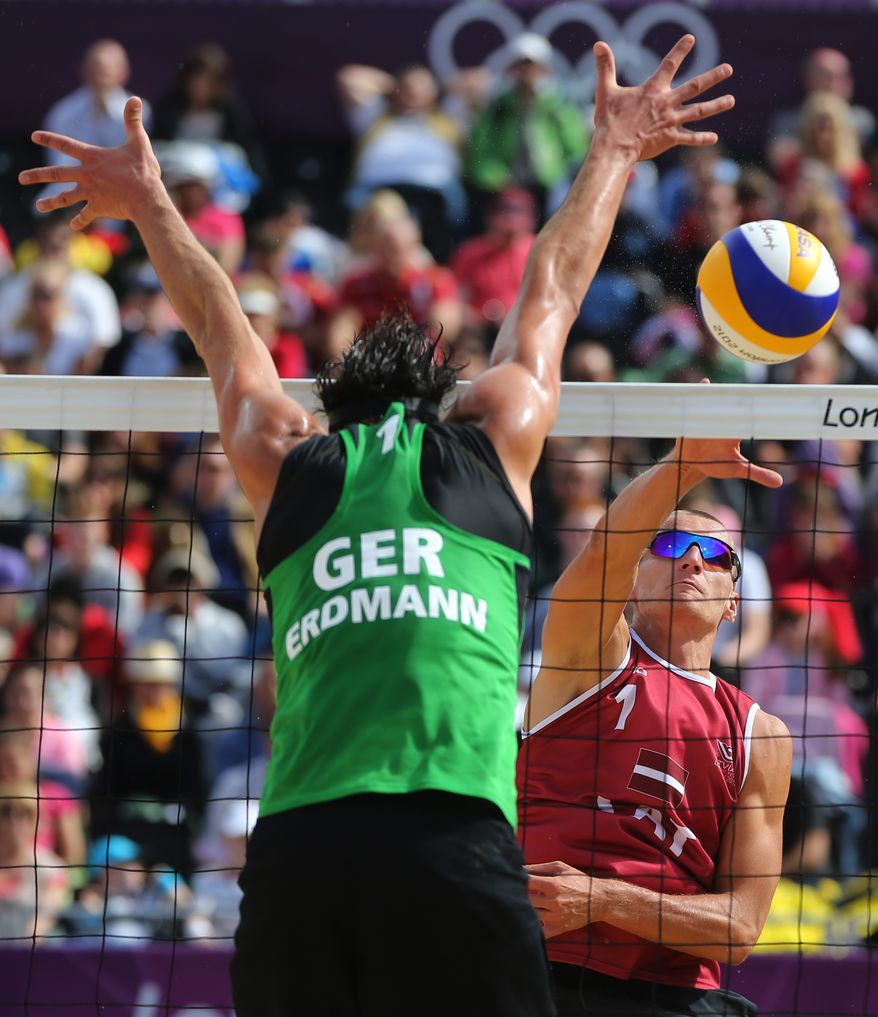 Jonathan Erdmann, left, from Germany tries to block Martins Plavins, right, from Latvia during their Beach Volleyball match at the 2012 Summer Olympics, Sunday, July 29, 2012, in London. (AP Photo/Petr David Josek)