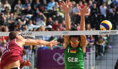 Jonathan Erdmann, right, from Germany tries to block Martins Plavins, left, from Latvia during their Beach Volleyball match at the 2012 Summer Olympics, Sunday, July 29, 2012, in London. (AP Photo/Petr David Josek)