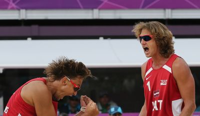 Ruslans Sorokins, left, from Latvia celebrates with his teammate Aleksandrs Samoilovs, right, after defeating Poland in their Beach Volleyball match at the 2012 Summer Olympics, Saturday, July 28, 2012, in London. (AP Photo/Petr David Josek)