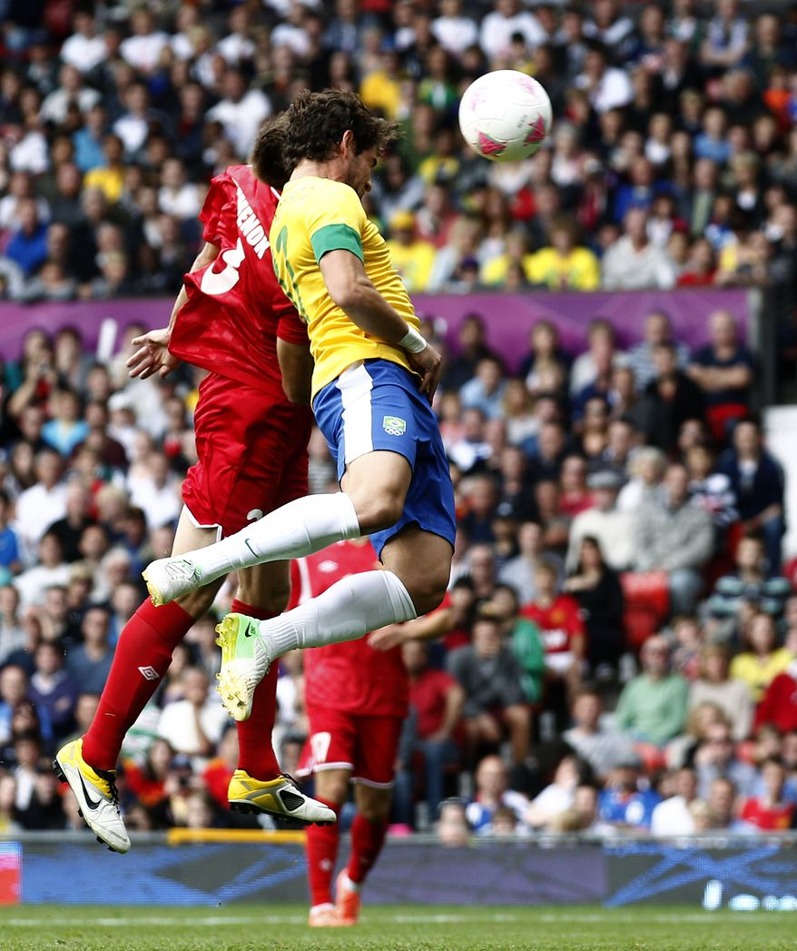 Brazil's Alexandre Pato, right, scores against Belarus as Igor Kuzmenok, left tries to gain control of the ball during their group C men's soccer match at the London 2012 Summer Olympics, Sunday, July 29, 2012, at Old Trafford Stadium in Manchester, England. (AP Photo/Jon Super)