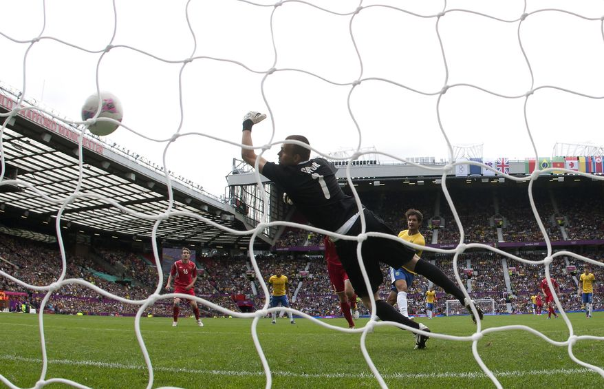 Brazil's Alexandre Pato, center right, scores past Belarus' goalkeeper Aleksandr Gutor during their group C men's soccer match at the London 2012 Summer Olympics, Sunday, July 29, 2012, at Old Trafford Stadium in Manchester, England. (AP Photo/Jon Super)