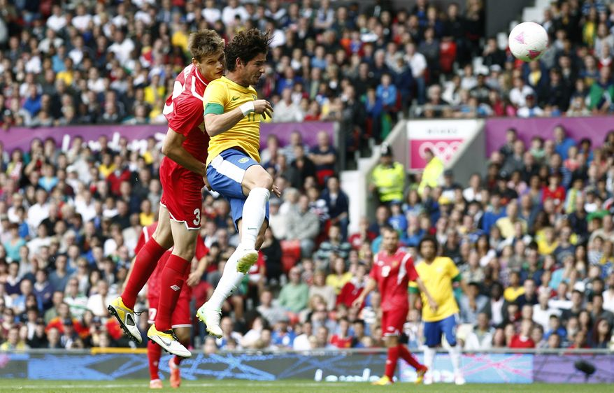 Brazil's Alexandre Pato, second from left, collides with Belarus' Igor Kuzmenok as he scores during their group C men's soccer match at the London 2012 Summer Olympics, Sunday, July 29, 2012, at Old Trafford Stadium in Manchester, England. (AP Photo/Jon Super)