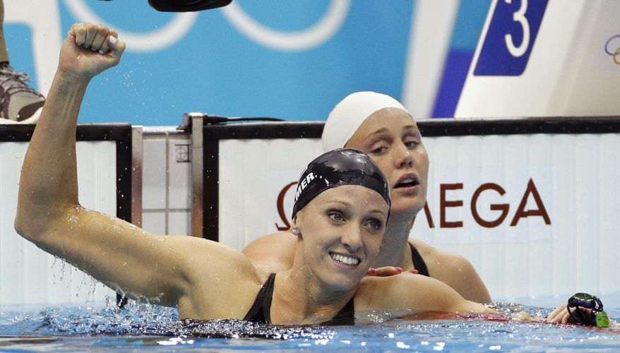 United States' Dana Vollmer, left, reacts after winning gold and setting a new world record alongside Denmark's Jeanette Ottesen Gray following the women's 100-meter butterfly swimming final at the Aquatics Centre in the Olympic Park during the 2012 Summer Olympics in London, Sunday, July 29, 2012. Vollmer set a new world record with a time of 55.98. (AP Photo/Michael Sohn)