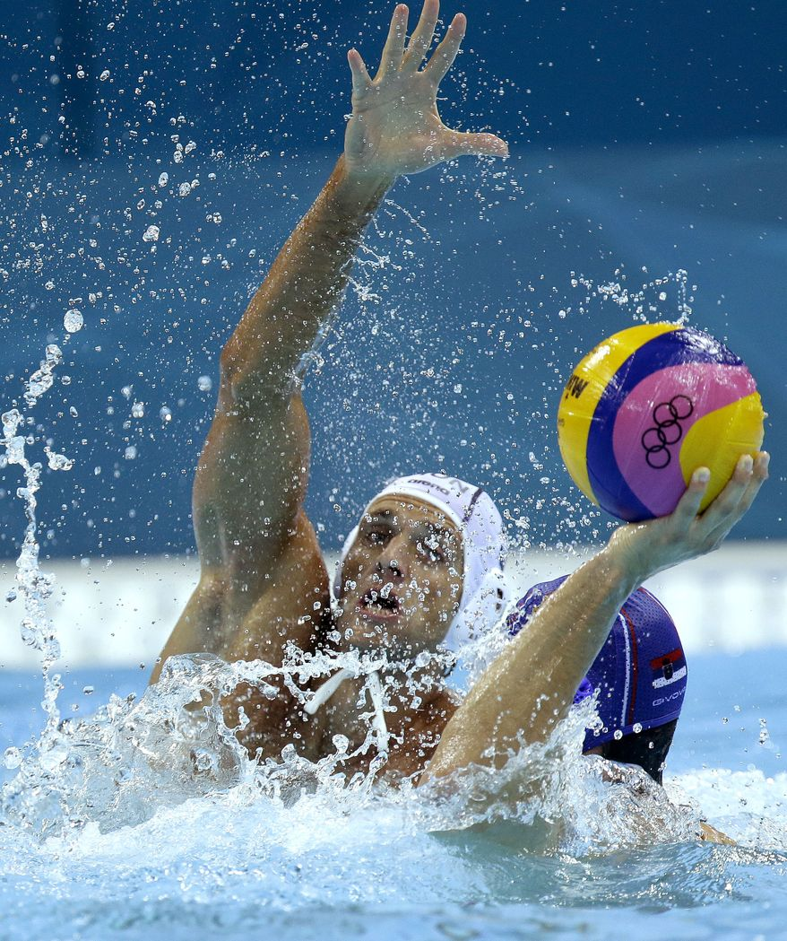 Tamas Kasas, left, of Hungary defends against Filip Filipovic of Sebia in a preliminary water polo match at the 2012 Summer Olympics, Sunday, July 29, 2012, in London. (AP Photo/Julio Cortez)