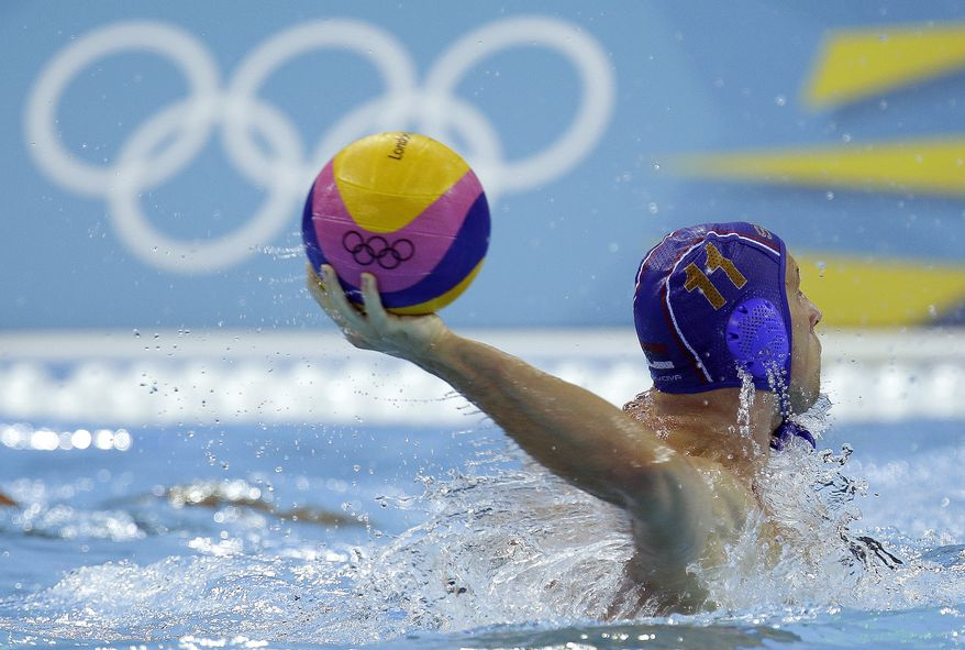 Andrija Prlainovic of Sebia prepares to shoot against Hungary in a preliminary water polo match at the 2012 Summer Olympics, Sunday, July 29, 2012, in London. Serbia won 14-10. (AP Photo/Julio Cortez)