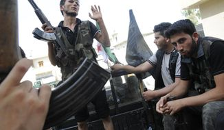 Syrian rebels sit July 28, 2012 in a pickup truck in Aleppo, Syria. (Associated Press)