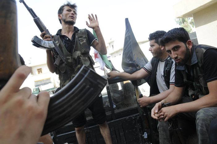 Syrian rebels sit July 28, 2012 in a pickup truck in Aleppo, Syria. (Associated Pr