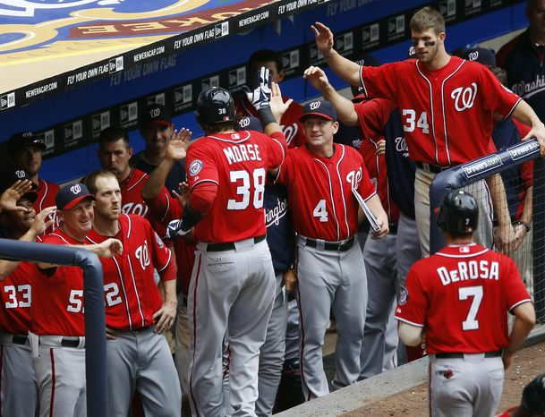 Washington Nationals' Michael Morse is greeted by his teammates after he hit a two-run home run off of Milwaukee Brewers' John Axford in the ninth inning of a baseball game, Sunday, July 29, 2012, in Milw