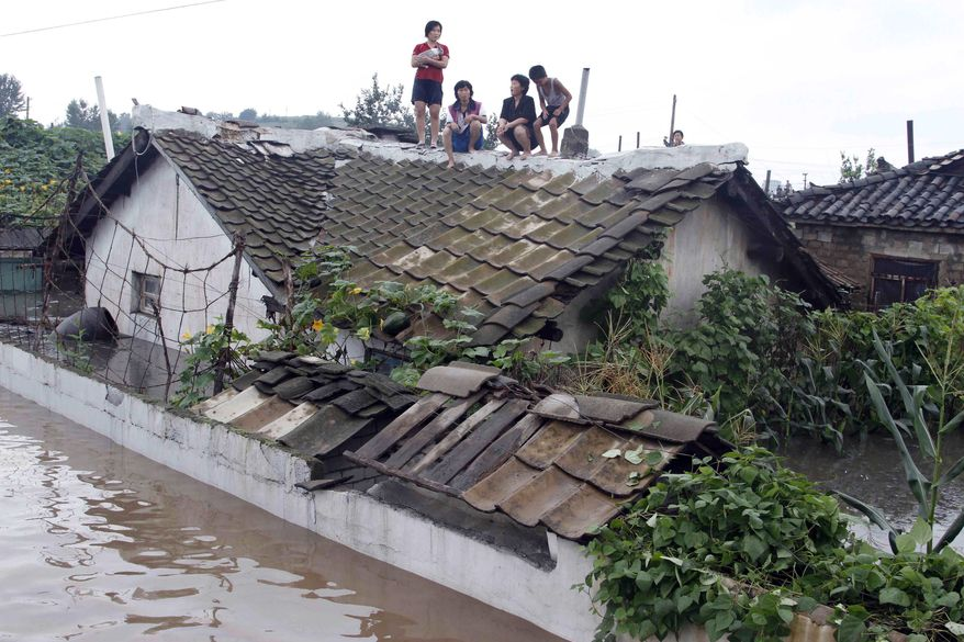 Residents wait on the roof of a flooded building in Anju City, South Phyongan province, North Korea on Monday. Officials said 1,000 houses and buildings were destroyed and 5,683 acres of farmland were completely submerged in the city. (Associated Press)