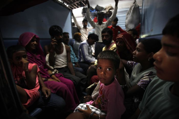 Passengers sit in a train and wait for power to get restored July 30, 2012, at a railway station in New Delhi. A major power outage struck northern India, plunging c