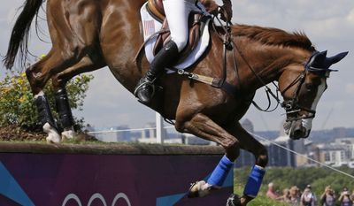 Karen O'Connor of the United States rides Mr Medicott as she competes in the equestrian eventing cross-country stage at the 2012 Summer Olympics, Monday, July 30, 2012, in London. (AP Photo/Ng Han Guan)