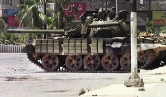 This image made from amateur video released by the Shaam News Network and accessed July 29, 2012, shows a Syrian military tank in Daraa, Syria. (Associated Press/Shaam News Network via AP video)