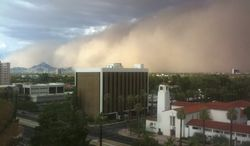 ** FILE ** A large dust storm, or haboob, sweeps across downtown Phoenix on July 21, 2012. (Associated Press)