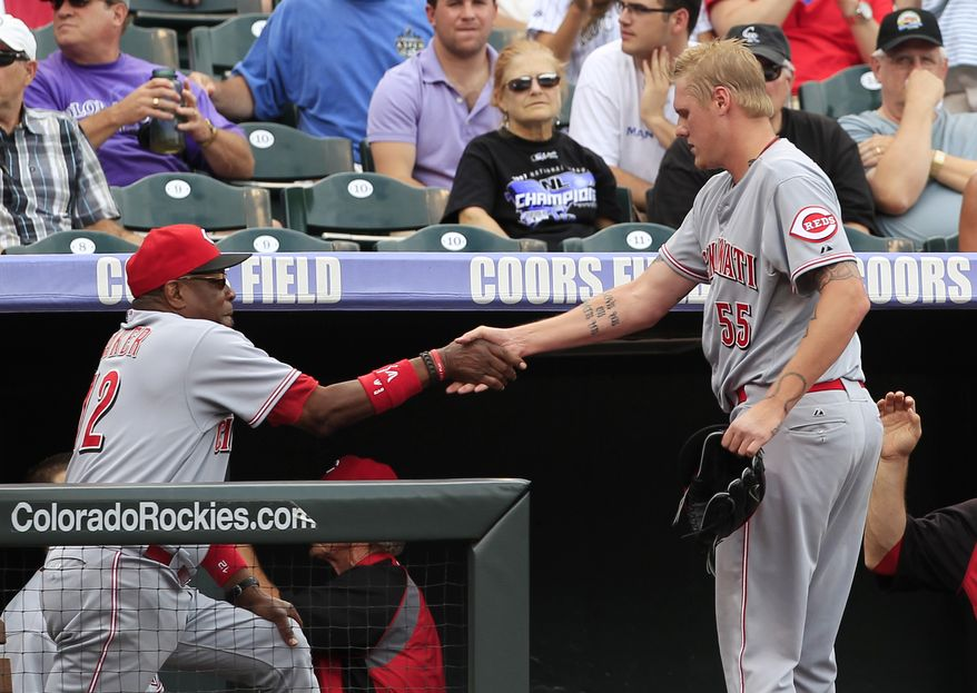 Cincinnati Reds manager Dusty Baker, left, congratulates starting pitcher Mat Latos who returns to the dugout after retiring the Colorado Rockies in the eighth inning of the Reds' 7-2 victory in a baseball game in Denver, Sunday, July 29, 2012. Latos earned his ninth victory of the season against three losses for his eight-inning effort. (AP Photo/David Zalubowski)