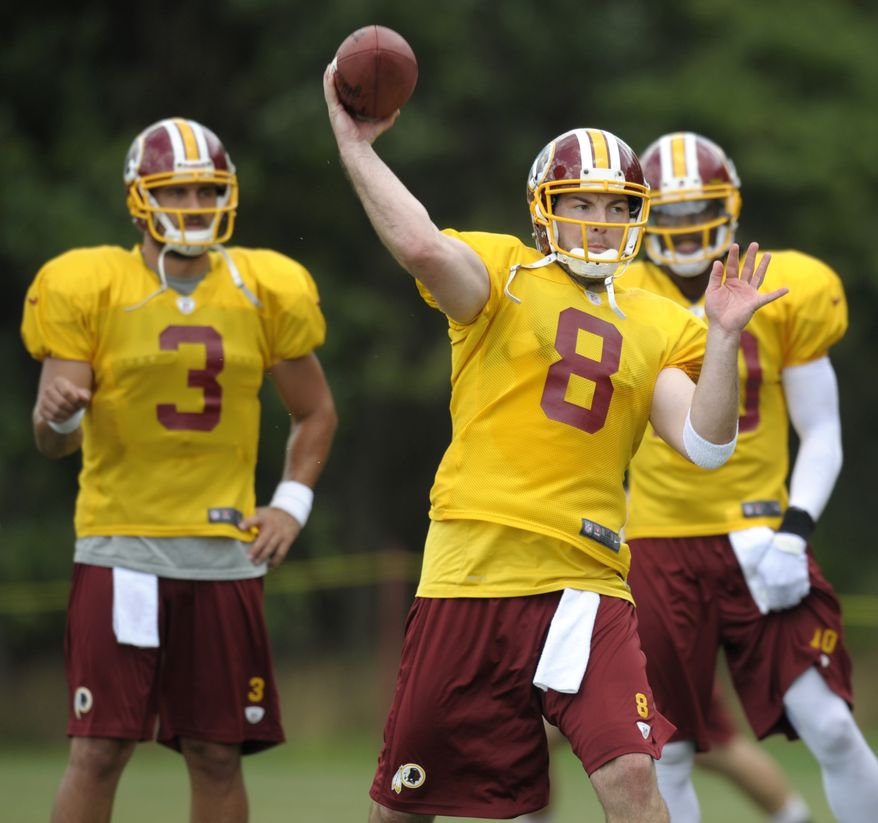 Washington Redskins quarterbacks Jonathan Crompton, left, and Robert Griffin III, right, watch as Rex Grossman (8) throws a ball during an afternoon practice session at NFL training camp at Redskins Park in Ashburn, Va., Saturday, July 28, 2012. (AP Photo/Cliff Owen)