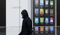 ** FILE ** A man walks by signs advertising Samsung Electronics Co.'s smartphone in Seoul on Jan. 28, 2011.  (Associated Press)