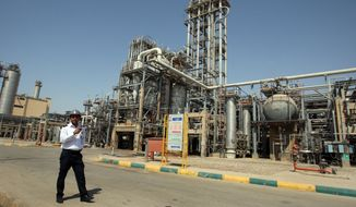 **FILE** An Iranian security guard stands Sept. 28, 2011, at the Maroun Petrochemical plant at the Imam Khomeini port in southwestern Iran. (Associated Press)