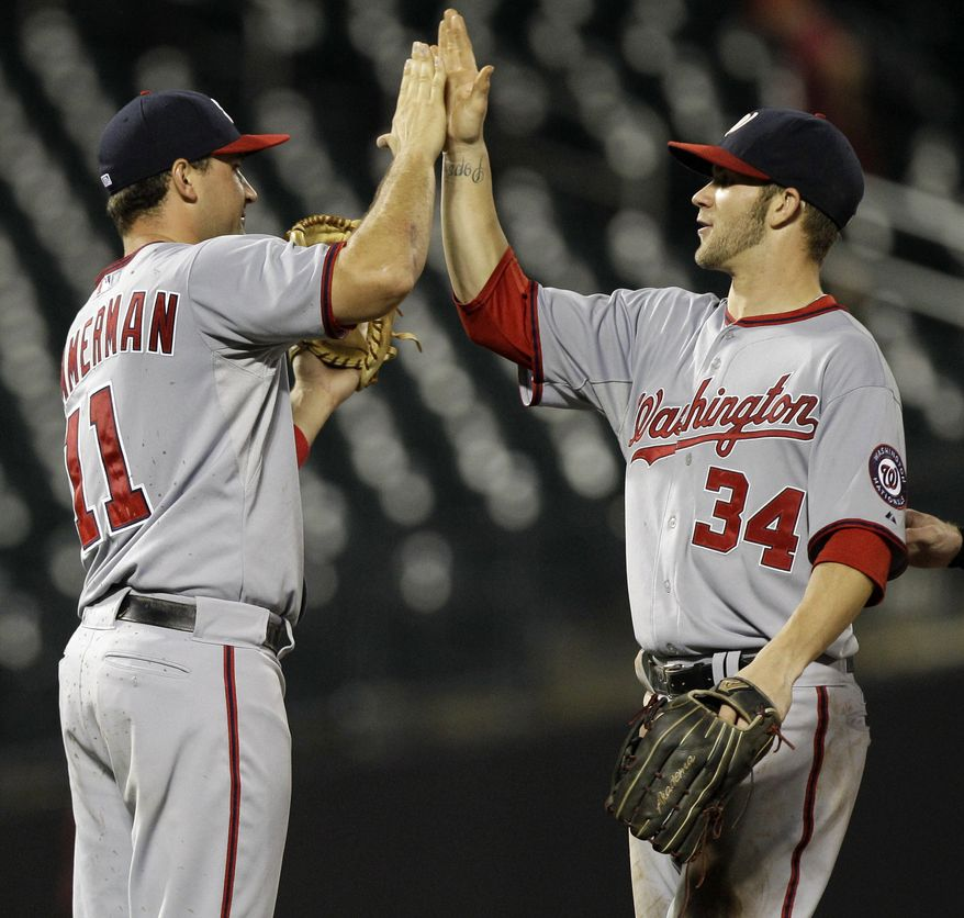 Washington Nationals third baseman Ryan Zimmerman (11) and right fielder Bryce Harper (34) celebrate after the Nationals defeated the New York Mets 8-2 in ten innings in their baseball game at Citi Field in New York, Monday, July 23, 2012. (AP Photo/Kathy Willens)