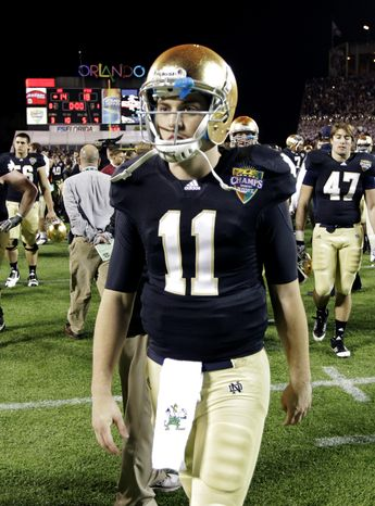 FILE - In this Dec. 29, 2011, file photo, Notre Dame quarterback Tommy Rees walks off the field after losing to Florida State 18-14 in the Champs Sports Bowl NCAA college football game in Orlando, Fla. Notre Dame has suspended Rees and linebacker Carlo Calabrese for the Sept. 1 season opener against Navy in Ireland, coach Brian Kelly announced Tuesday, July 31, 2012. (AP Photo/John Raoux, File)