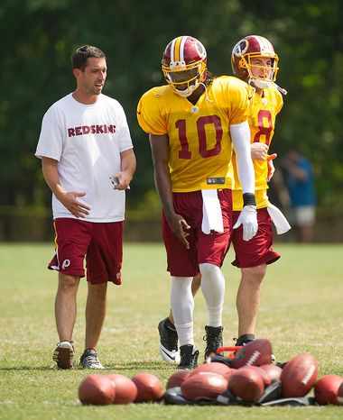 Washington Redskins offensive coordinator Shanahan, left, and  Washington Redskins quarterback Robert Griffin III (10), second from right, talk together as Washington Redskins quarterback Rex Grossman (8), right, jogs by during afternoon practice at the