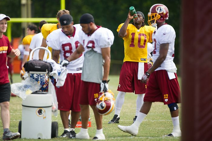 Washington Redskins quarterback Robert Griffin III (10), second from right, takes a water break with teammates during afternoon practice at the Washington Redskins training camp at Redskins Park, Ashburn, Va., Washington, D.C., Monday, July 30, 2012. (Andrew Harnik/The Washington Times)