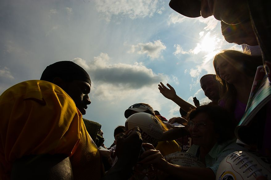 Washington Redskins quarterback Robert Griffin III (10) signs autographs for fans following afternoon practice at the Washington Redskins training camp at Redskins Park, Ashburn, Va., Washington, D.C., Monday, July 30, 2012. (Andrew Harnik/The Washington Times)