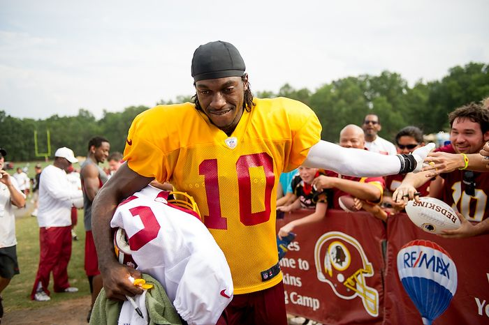 Washington Redskins quarterback Robert Griffin III (10) high fives fans following afternoon practice at the Washington Redskins training camp at Redskins Park, Ashburn, Va., Washington, D.C., Monday, July 30, 2012. (Andrew Harnik/The Washington Times)