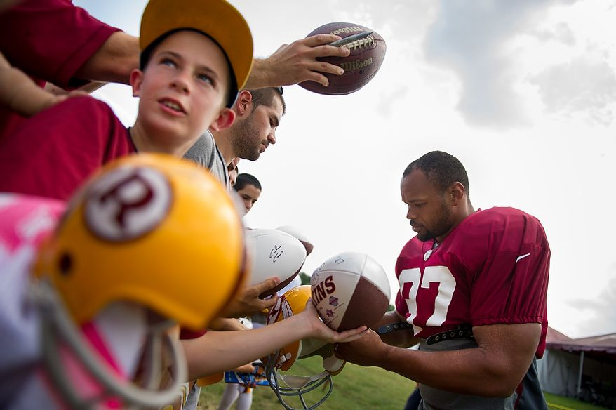 Washington Redskins linebacker Lorenzo Alexander (97) signs autographs for fans before afternoon practice at the Washington Redskins training camp at Redskins Park, Ashburn, Va., Washington, D.C., Monday, July 30, 2012. (Andrew Harnik/The Washington Times)