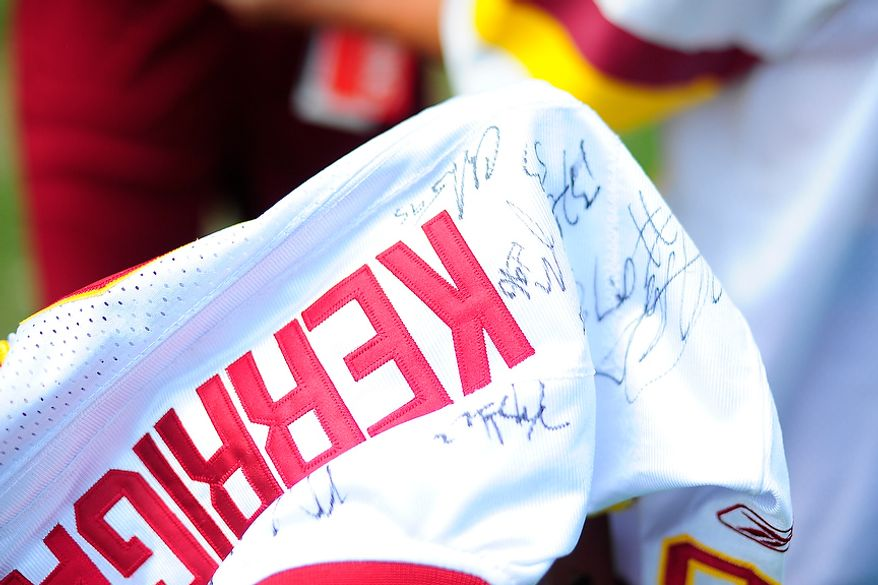 A fans' Ryan Kerrigan jersey is autographed by several Redskins' players during Redskins' training camp at Redskins Park, Ashburn, Va., Monday, July 30, 2012.  (Ryan M.L. Young/The Washington Times)