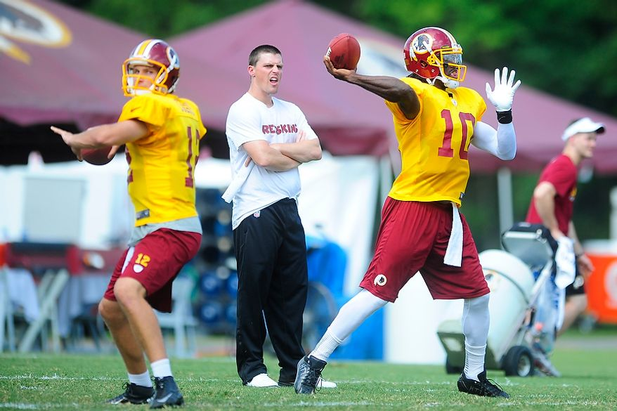 Robert Griffin III (#10) and Kirk Cousins (#12) participate in drills during Redskins' training camp at Redskins Park, Ashburn, Va., Monday, July 30, 2012.  (Ryan M.L. Young/The Washington Times)