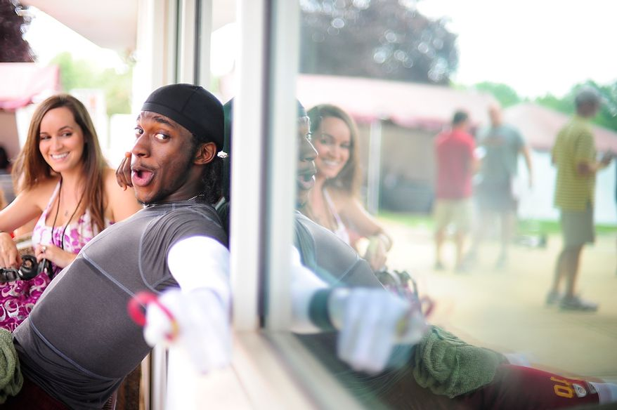 Robert Griffin III has a laugh on a bench outside of Redskins' facilities while joking with members of the media with his fiance Rebecca Liddicoat following Redskins' training camp at Redskins Park, Ashburn, Va., Monday, July 30, 2012.  (Ryan M.L. Young/The Washington Times)