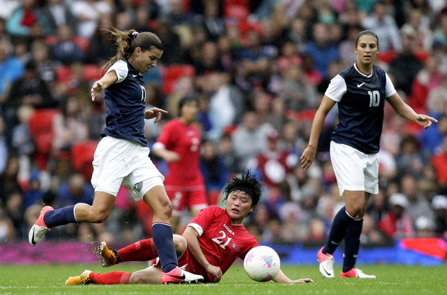 North Korea's Kim Su Gyong, bottom, fights for the ball against United States' Tobin Heath, left, as Carli Lloyd watches during their group G women's soccer match at the London 2012 Summer Olympics, Tuesday, July 31, 2012 at Old Trafford Stadium in Manchester, England. (AP Photo/Jon Super)