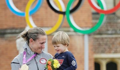 Gold medalist Kristin Armstrong, of the United States, kisses her son Lucas, after winning the women's individual time trial cycling event at the 2012 Summer Olympics, Wednesday, Aug. 1, 2012, in London. (AP Photo/Sergey Ponomarev)