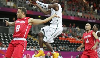 Nigeria's Tony Skinn, center, drives to the basket behind Tunisia's Marouan Kechrid, left, during a basketball game at the 2012 Summer Olympics, Sunday, July 29, 2012, in London. At right is Tunisia's Radhouane Slimane. (AP Photo/Charles Krupa)