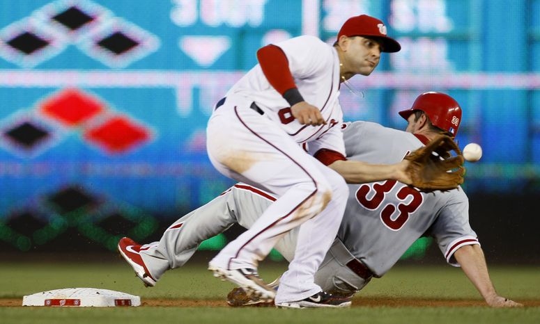 Washington Nationals second baseman Danny Espinosa (8) takes the throw as Philadelphia Phillies' Cliff Lee (33) steals second in the fourth inning of a baseball game at Nationals Park, Tuesday, July 31, 2012, in Washington. The Phillies won 8-0. (AP Photo/Carolyn Kaster)