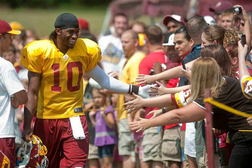 Washington Redskins quarterback Robert Griffin III (10) greets fans before start of training camp at Redskins Park on Wednesday, August 1, 2012, in Ashburn, Va. (Raymond Thompson/The Washington Times)