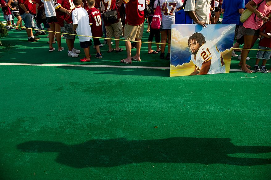 Painter Freddy Larkin of Upper Marlboro, Md. stands with his portrait of deceased Washington Redskins Sean Taylor following afternoon practice at training camp at Redskins Park, Ashburn, Va., Wednesday, August 1, 2012. (Andrew Harnik/The Washington Times)