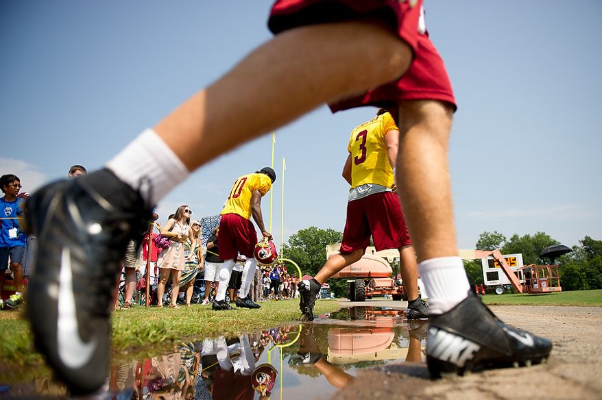 Washington Redskins quarterback Robert Griffin III (10), left, and Washington Redskins quarterback Jonathan Crompton (3), right, make their way to the field for afternoon practice at training camp at Redskins Park, Ashburn, Va., Wednesday, August 1, 2012. (Andrew Harnik/The Washington Times)