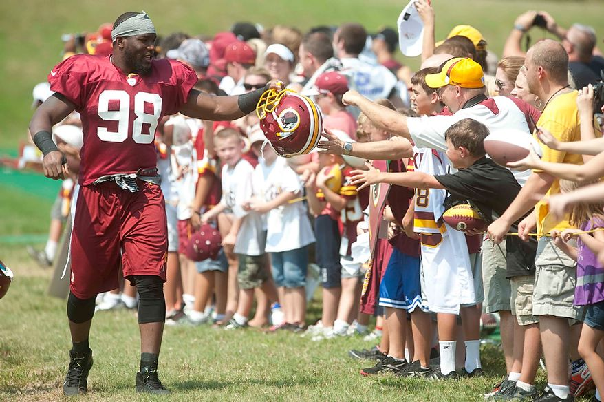 Washington Redskins linebacker Brian Orakpo (98) greets fans as he enters the practice field during training at Redskins Park on Wednesday, August 1, 2012, in Ashburn, Va. (Raymond Thompson/The Washington Times)