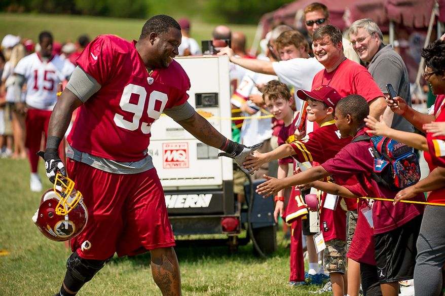 Washington Redskins defensive tackle Jarvis Jenkins (99) high fives young fans as he makes his way to afternoon practice at training camp at Redskins Park, Ashburn, Va., Wednesday, August 1, 2012. (Andrew Harnik/The Washington Times)