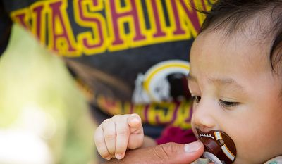 3 month old Ezra Ramira of Chantilly, Va., works on his football pacifier in the shade during afternoon practice at training camp at Redskins Park, Ashburn, Va., Wednesday, August 1, 2012. (Andrew Harnik/The Washington Times)