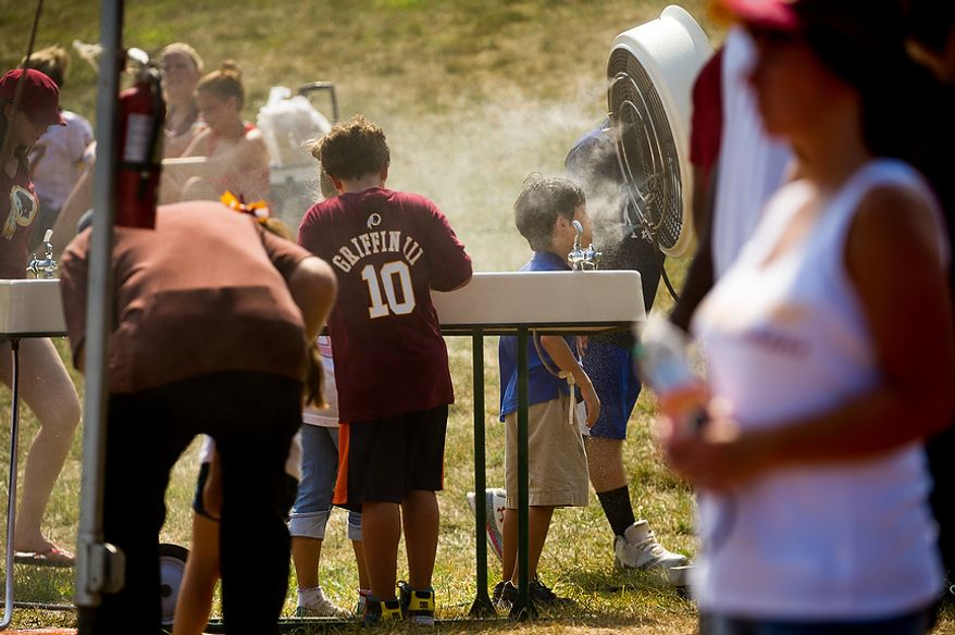 A young fan cools off in a water mist fan during afternoon practice at training camp at Redskins Park, Ashburn, Va., Wednesday, August 1, 2012. (Andrew Harnik/The Washington Times)