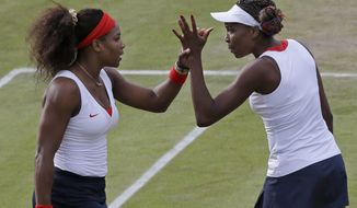 Serena Williams, left, and Venus Williams of the United States clasp hands as they compete against Sorana Cirstea and Simona Halep of Romania in women's doubles at the All England Lawn Tennis Club in Wimbledon, London at the 2012 Summer Olympics, Monday, July 30, 2012. (AP Photo/Elise Amendola)