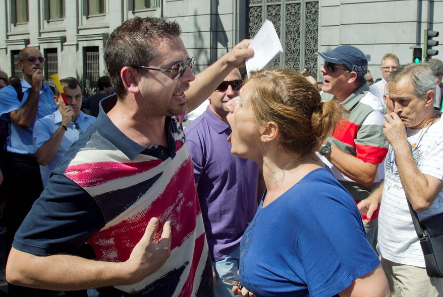 A motorist who got out of her car argues with a demonstrator as civil servants blocked traffic during a protest against government cuts in Madrid on Monday. Spanish Prime Minister Mariano Rajoy has been introducing successive rounds of austerity measures aimed at preventing the country from being forced into a public finance bailout. (Associated Press)
